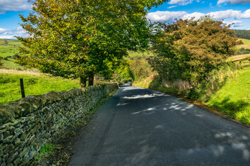 Downhill countryside road, Summer, blue sky and white clouds, Forest Of Bowland, Lancashire, England, UK