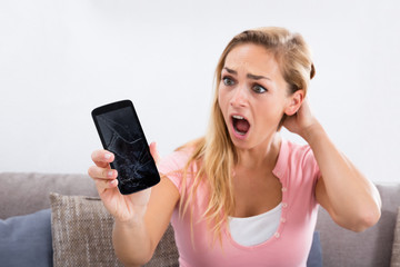 Shocked Woman Holding Damaged Phone