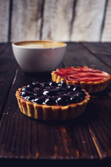 Berry tarts with strawberries and blueberries next Cup of coffee