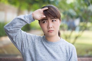 Woman has head ache at the park