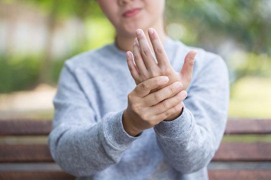 Woman has hand pain at park