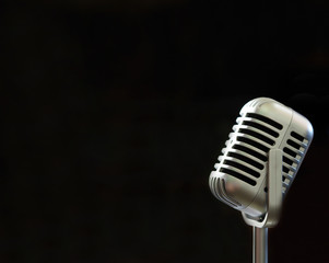Vintage microphone with blurred black background and soft focus