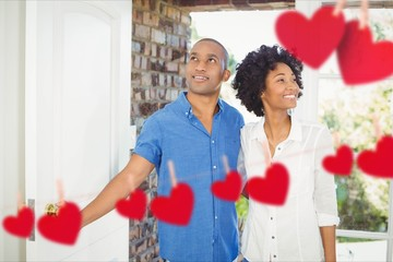 Composite image of red hanging hearts and couple entering home