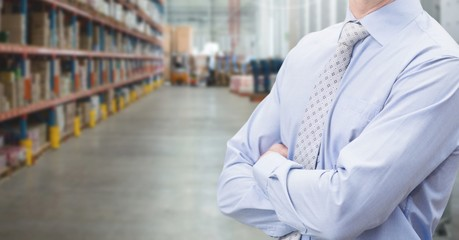 Manager standing with arms crossed in warehouse
