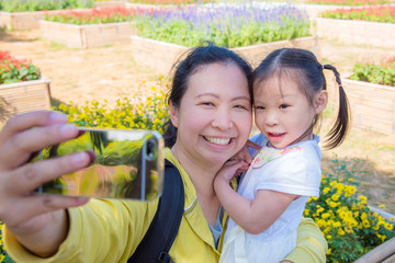 Asian mother taking photo with her daughter by smart phone