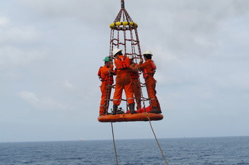 Workers are lifted by the crane to the offshore platform, Transfer crews by personal basket from the platform to crews boat