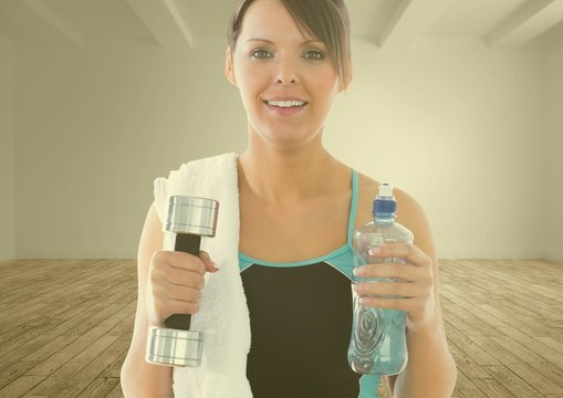 Portrait of fit woman holding dumbbell and water bottle