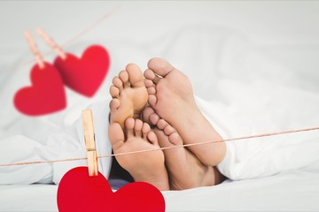 Composite image of red hanging hearts and couple lying on bed