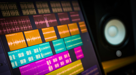 colorful digital waveform on computer monitor and studio speakers for sound recording concept