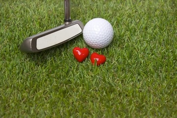 Golf ball and putter are on the green course with love sign