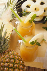 freshly squeezed pineapple juice in a glass jar closeup. vertical