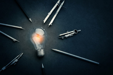 drawing tool with glow light bulb on leather background creativi
