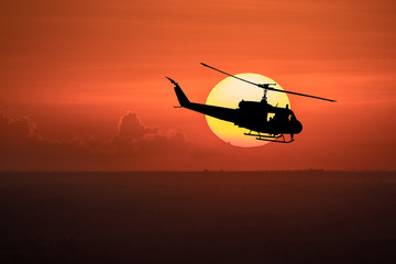 Flying helicopter silhouettes on sunset background.