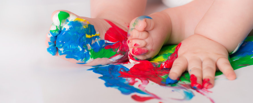 Baby child draws with colored paints hands, dirty feet.  Selective focus