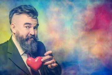 Adult bearded man in a suit holding red heart on a multicolor background