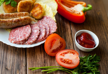 Grilled sausages and meat with vegetables and sauce on the table. On the wooden background, banner for cafe