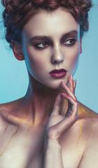Girl with golden makeup posing in studio