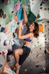 woman bouldering in climbing gym