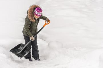 Woman cleans snow shovel