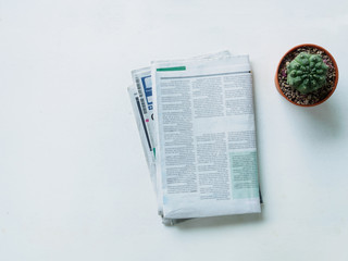 Top view stack newspaper and cactus on white dask