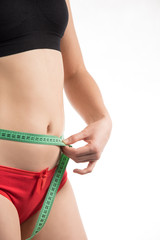Girl on a diet measuring waist and abdomen centimeter and looks