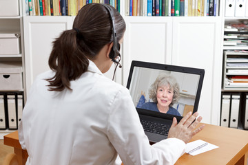 geriatric doctor headset laptop patient