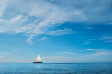 Sail boat on horizon at sea with blue sky and clouds