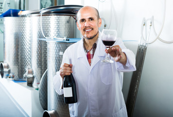 mature man in white coat having glass with wine in hands at fact
