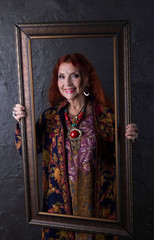 Redhead woman in ethnic jewelry and embroidered oriental coat fun laughs holding a picture frame on background the dark walls