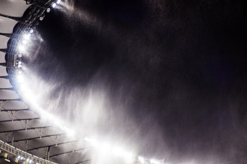 against the background of a sports stadium floodlights, flying snow