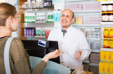 Pharmaceutist helping adult woman in drugstore