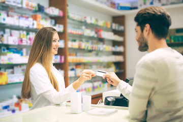 Experienced pharmacist counseling male customer in modern pharma