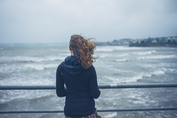 Young woman by the sea on stormy day