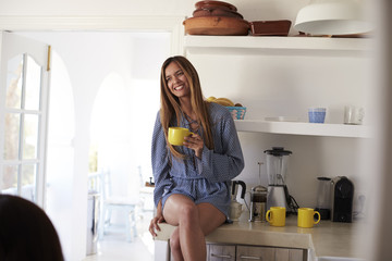 Young woman sitting on kitchen worktop holding cup, Ibiza