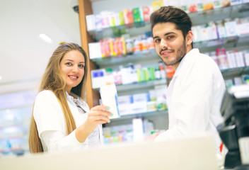 Female and male pharmacists in pharmacy smiling