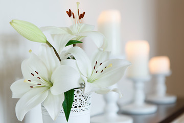 White lilies in a vase against a backdrop of candles. Flowers. Postcard