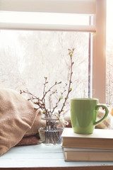 Cup of coffee books branch of cherry tree wool blanket on windowsill. In the background snow tree pattern on window. Cozy home concept.