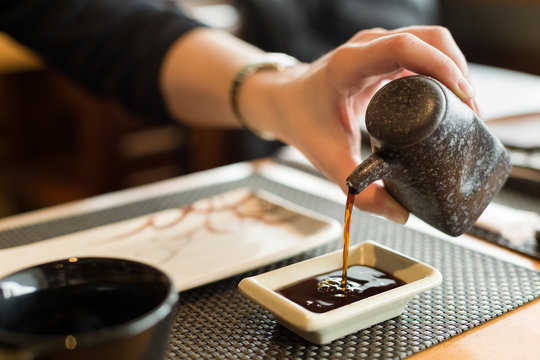 Closeup of woman's hand pouring soy sauce. Japanese food. Asian dinner.