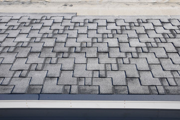 Close up view on unfinished Asphalt Roofing Shingles Background. Unfinished Roof Shingles - Roofing. Roof shingles covered with frost
