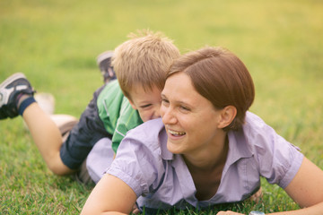 happy blond caucasian kid outdoor family portrait at park with his mum