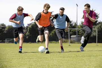 Middle schoolboys and teacher running playing soccer on field in physical education class