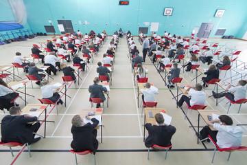 Middle school students taking examination at desks in school gymnasium