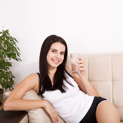 Girl drinking water at home. Glass of water in morning before breakfast.