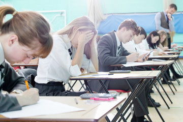 Stressed female middle school student taking examination at desks in school gymnasium with head in hands