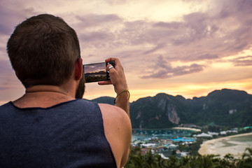 Guy taking photo of the sunset on his phone