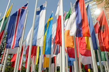 Nationale Flaggen flattern bei Wind und Sonne an Fahnenmasten, Flaggen-Parade