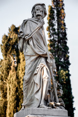 The blindfolded Grim Reaper Death personified statue at the cemetery, on cypress background