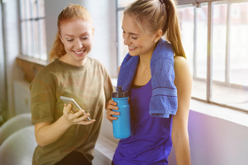 frauen mit wasserflasche und handy im fitness-studio