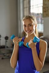 lächelnde frau mit hanteln im fitnessstudio