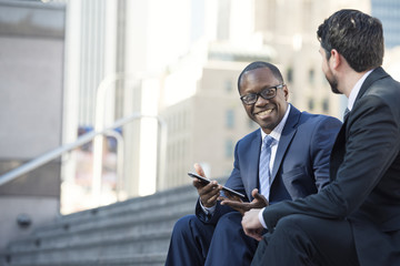 Smiling businessmen sitting on stairs sharing tablet with colleague